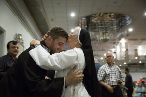 Newly ordained, the Rev. David Stephan receives a kiss from his aunt during a reception at St. Peter Chaldean Cathedral in El Cajon. A Dominican Sister of St. Catherine of Siena, she traveled from Iraq to be with the family for his ordination. (photograph by Nancy Wiechec)
