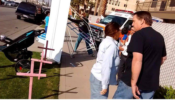 The man in the black shirt attacked and harassed pro-life advocate Terri Palmquist (in white shirt) while other woman knocked over the ladder used by pro-lifers and damaged their cameras. Meanwhile, and abortion clinic patient suffering a medical emergency is loaded in to an ambulance. The man was later arrested for vandalism after destroying the memorial crosses. (photo: Terry and Tim Lindquist)