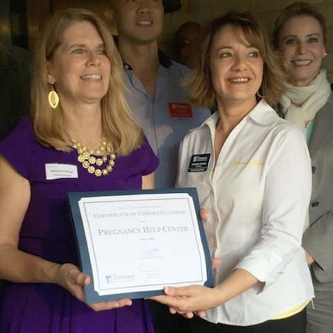 Adrienne Gross of the Pregnancy Help Center receives a certificate in recognition from Marianne Brooks of the Torrence Chamber of Commerce April 8, the day the center celebrated 40 years of service. (photo from Angelus article)