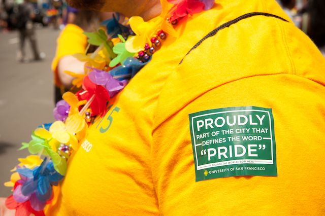"2015 Gay Pride Parade attendee wears a sticker emblazoned with the USF logo with the words ""proudly part of the city that defines the word 'pride' "" (photo from USF website)"