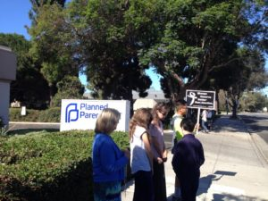 """Prayer warriors and sidewalk counselors. One person holds a sign saying, """"women deserve better than abortion."""""""