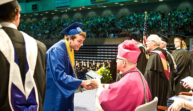 A Santa Margarita Catholic high school student receives his diploma from Bishop Kevin Vann during the school's commencement ceremony at the Bren Events Center. (photo: OC Register)