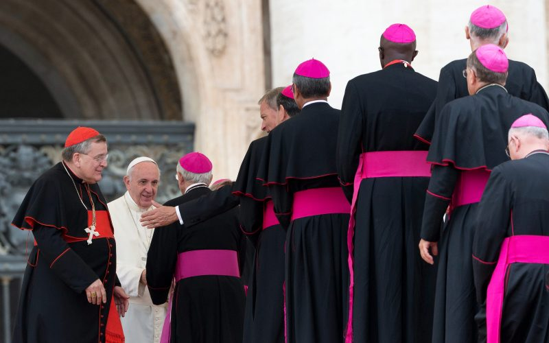 Cardinal Raymond Burke, left, stands by Pope Francis saluting bishops, at the end of a general audience in St. Peter's Square (AP)