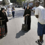 Small band of friars and nuns in habits feed homeless in Los Angeles